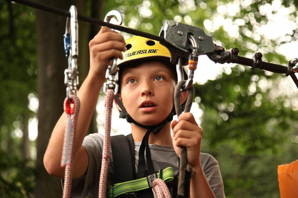 Kid doing adventure with all the safety equipment
