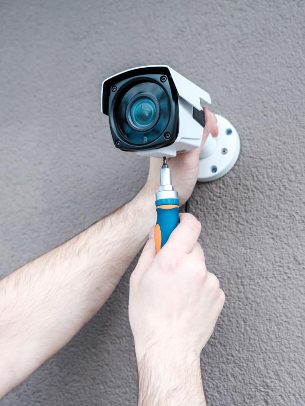 close up hands technician adjusting cctv camera